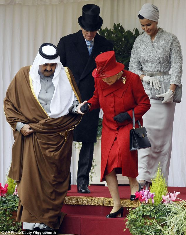 Sheik Hamad bin Khalifa Al-Thani helps the Queen down some steps as they head off to review the Guard of Honour