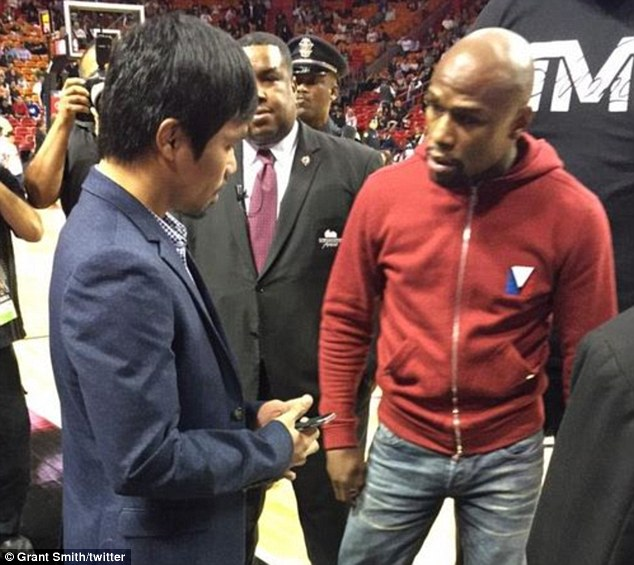 Manny Pacquiao (left) and Floyd Mayweather meeting at a basketball in Miami on Tuesday