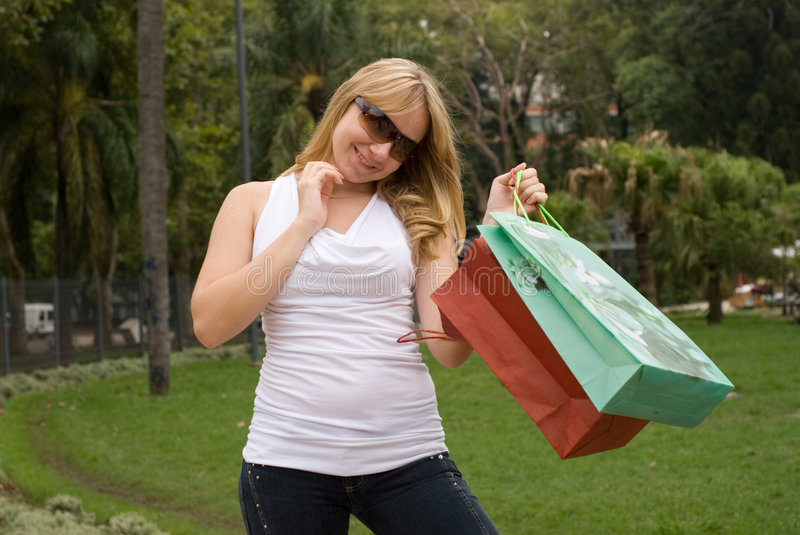 Beautiful teenager with shopping bags. On the nature royalty free stock photo