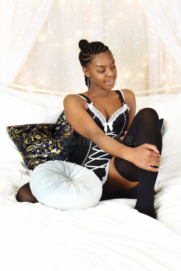 Beautiful Female Black Teenager. Beautiful young black teenager wearing lingerie sitting on a white satin bed with rich cushions in a fairy-tale setting looking royalty free stock image