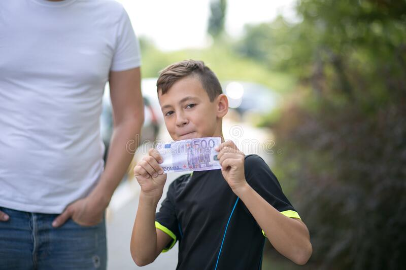 Cute teenager boy with money euro in hand. royalty free stock image