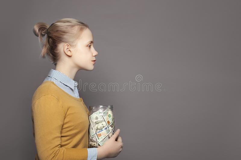 Cute young girl teenager saving money in glass jar. Education fees and saving money concept. royalty free stock image