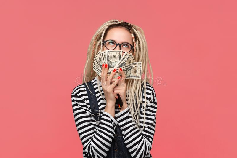 Excited teenager with dreadlocks in a striped shirt and jeans jumpsuit holding lots of cash. Being rich royalty free stock image