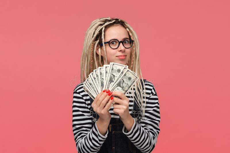 Excited teenager with dreadlocks in a striped shirt and jeans jumpsuit holding lots of cash. Being rich stock images