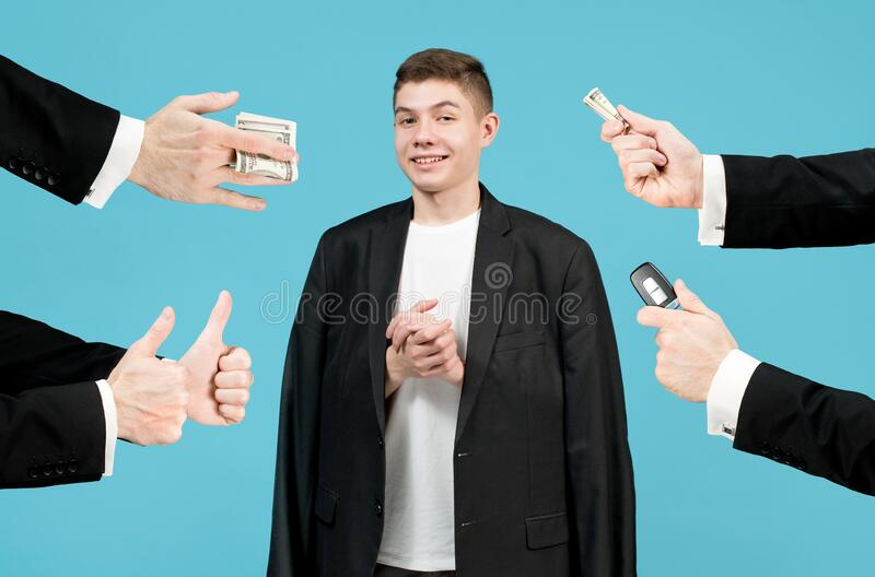 Image of a wealthy teenager with a rich dad. The teenager smiles slyly, he wears a very large jacket of his father and the hands of a respectable men from royalty free stock photo