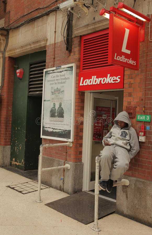 Ladbrokes betting shop. Hooded teenager sitting in front of Ladbrokes betting shop in Victoria station, London, UK stock photo