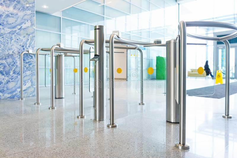 Stylish turnstiles made of glass and metal in the lobby of an unrecognizable business center. Modern control and security systems. Access system in an office stock images