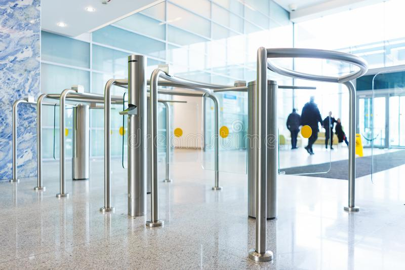 Stylish turnstiles made of glass and metal in the lobby of an unrecognizable business center. Modern control and security systems. Access system in an office royalty free stock photos
