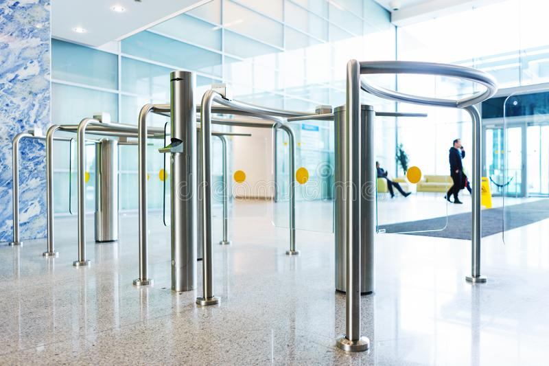 Stylish turnstiles made of glass and metal in the lobby of an unrecognizable business center. Modern control and security systems. Access system in an office royalty free stock photo