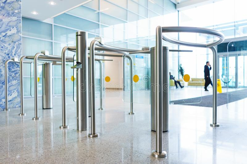 Stylish turnstiles made of glass and metal in the lobby of an unrecognizable business center. Modern control and security systems. Access system in an office stock photography