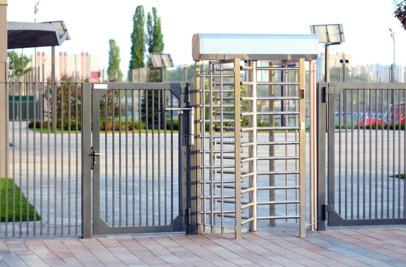 Protected entrance gate.Entrance to office through big in full human growth stainless steel turnstiles. Concept of security, lock. Gates, business, dangerous stock photo