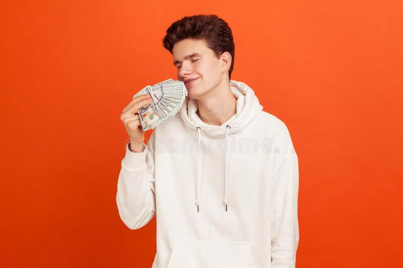 Satisfied rich teenager in casual hoodie enjoying smell of dollars with closed eyes, inherit large amount of money, spender. Indoor studio shot isolated on stock photography
