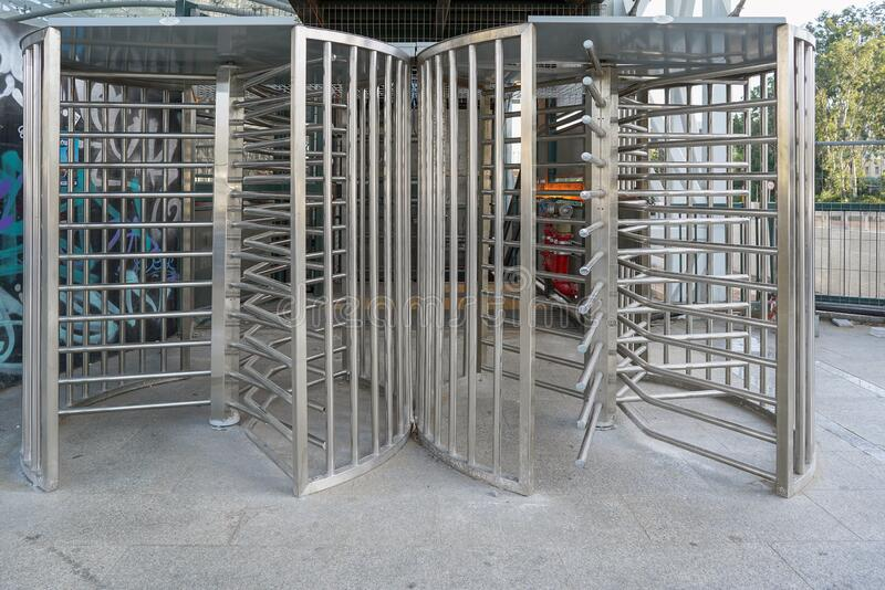 Steel revolving turnstiles at the entrance of production or metro station. Steel revolving security turnstile on the street. Protected entrance gate - secured royalty free stock image
