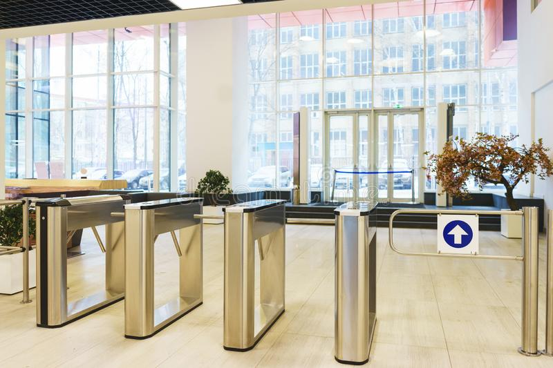 Stylish turnstiles made of glass and metal in the lobby of an unrecognizable business center. Modern control and security systems. Access system in an office stock photos