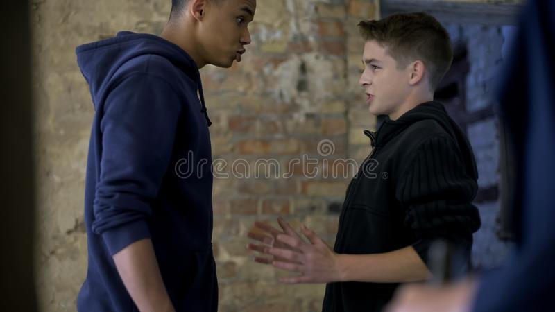 Teen humiliating nerd, poor teenager bullying rich boy, adolescent aggression. Stock photo stock photo