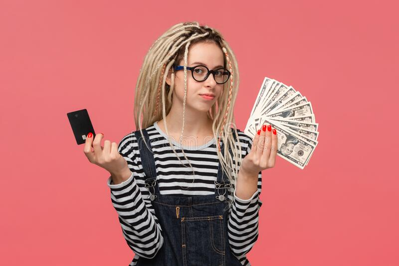 Teenager with dreadlocks in a striped shirt and jeans jumpsuit choosing between cash and bank card. stock photos