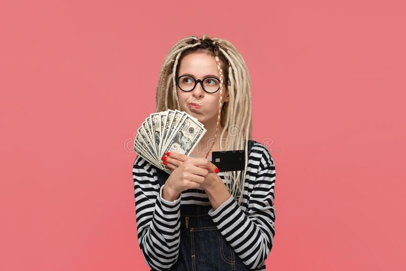 Teenager with dreadlocks in a striped shirt and jeans jumpsuit choosing between cash and bank card. stock photography