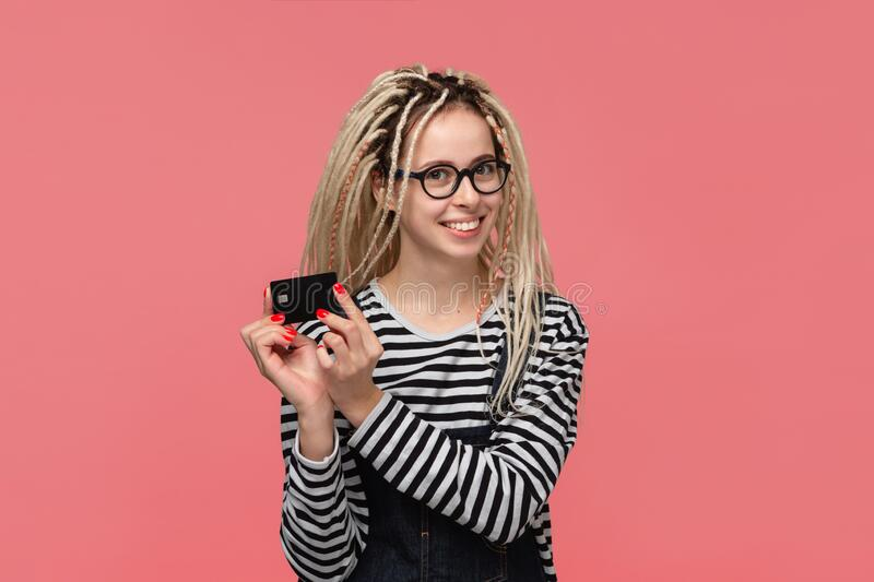 Teenager with dreadlocks in a striped shirt and jeans jumpsuit holding bank card. Pay with card stock photos