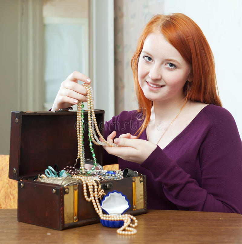 Teenager girl looks jewelry in treasure chest at home. Portrait of red-headed teenager girl looks jewelry in treasure chest at home stock photography
