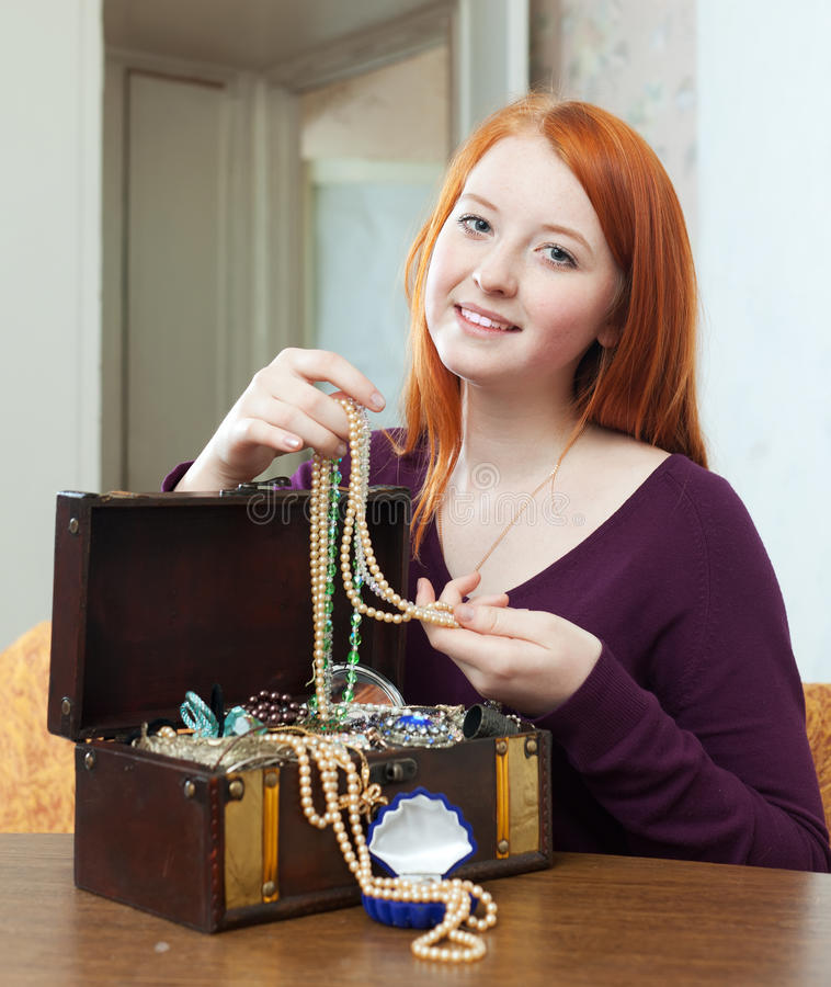 Teenager girl looks jewelry in treasure chest. Portrait of red-headed teenager girl looks jewelry in treasure chest at home interior stock photo