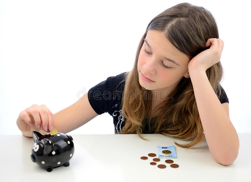 Teenager making euro money savings. Portrait of teenager laying diverse euro money in to the piggy-bank stock images