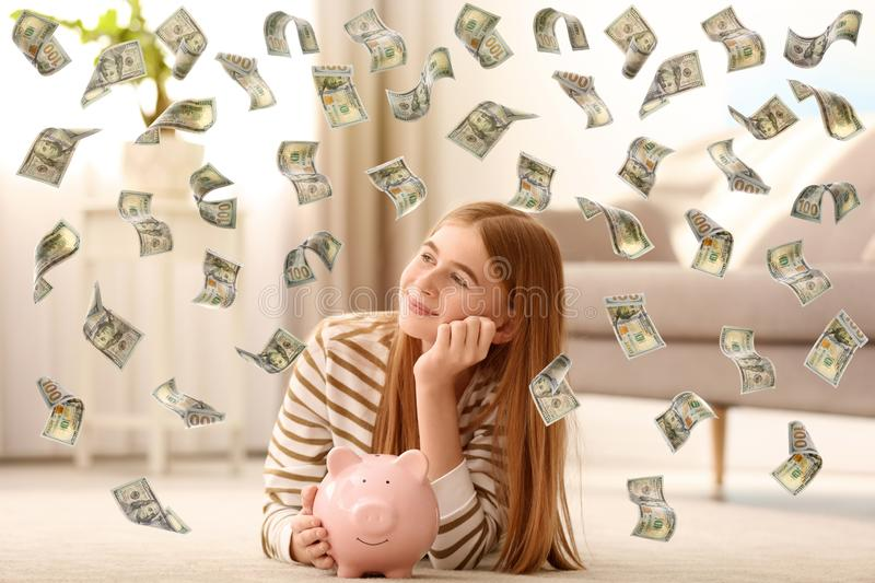 Teenager with piggy bank and flying money. At home royalty free stock images