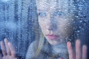 woman looking sad out of the window